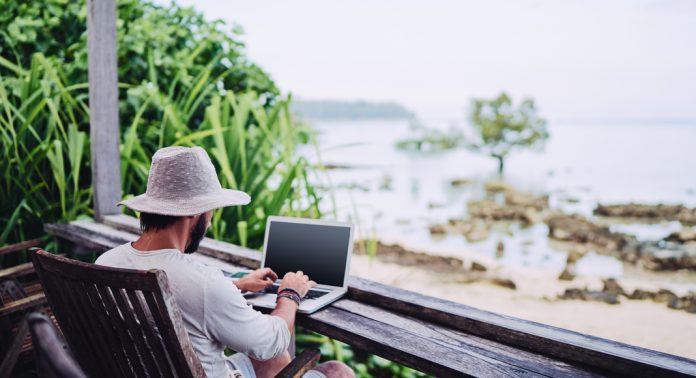 Un homme travaille sur son ordinateur en face de la mer